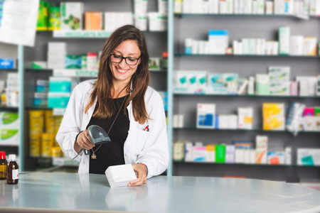 Beautiful Pharmacist at Work in a Drugstore photo
