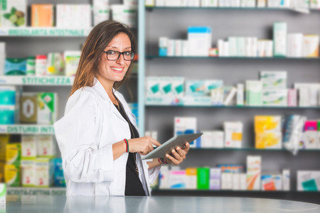 Beautiful Pharmacist with Digital Tablet in a Drugstore Imagens
