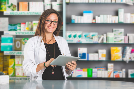 Beautiful Pharmacist with Digital Tablet in a Drugstore photo
