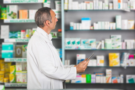 Handsome Pharmacist with Digital Tablet in a Drugstore photo