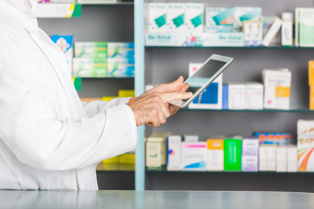 Handsome Pharmacist with Digital Tablet in a Drugstore