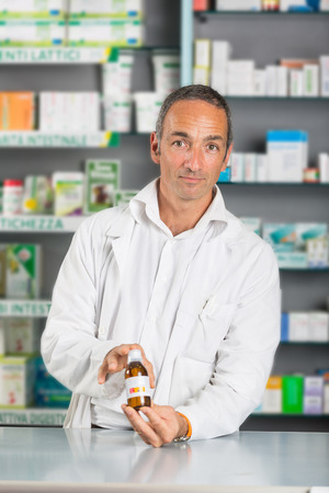 Handsome Pharmacist at Work in a Drugstore photo