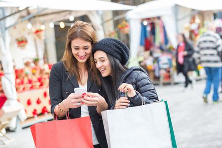 Mujeres felices con el teléfono inteligente y bolsos de compras Foto de archivo - 35484396