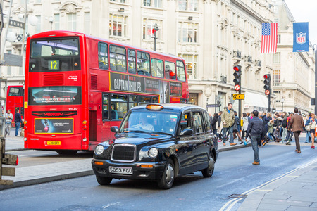 LONDON, UNITED KINGDOM - OCTOBER 25, 2013: Famous Black Cab and Double-Decker Red Bus next to Oxford Circus with people crossing the street on background.