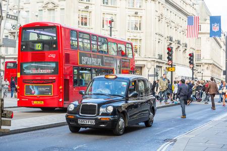 personas en la calle: LONDRES, Reino Unido - 25 de octubre 2013: Famoso Negro Cab y Double-Decker autobús rojo junto a Oxford Circus con la gente que cruza la calle en el fondo.