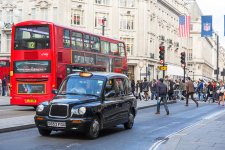 doubledecker: LONDON, UNITED KINGDOM - OCTOBER 25, 2013: Famous Black Cab and Double-Decker Red Bus next to Oxford Circus with people crossing the street on background.