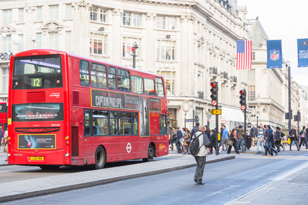 oxford street: LONDON, UNITED KINGDOM - OCTOBER 25, 2013: Famous Double-Decker Red Bus next to Oxford Circus with people crossing the street on background.