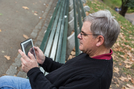 greying: Retired Senior Man at Park, Typing on Digital Tablet Stock Photo