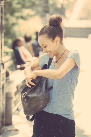 newyork: Beautiful Mixed-Race Young Woman Looking Inside Her Bag