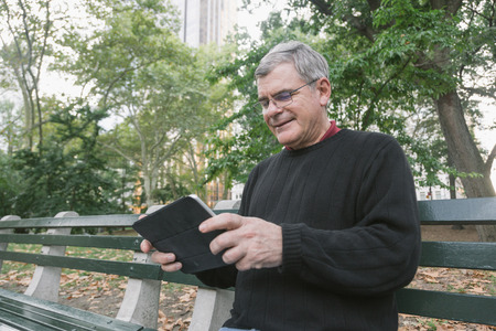 grizzled: Retired Senior Man at Park, Typing on Digital Tablet Stock Photo