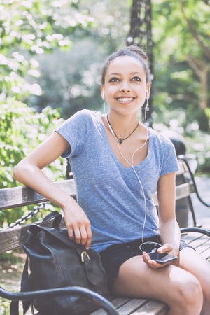 newyork: Beautiful Mixed-Race Young Woman Listening Music With Earphones at Park