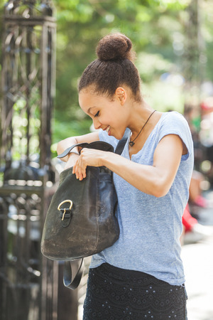 looking inside: Beautiful Mixed-Race Young Woman Looking Inside Her Bag