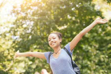 arms up: Beautiful Mixed-Race Young Woman at Park, Sense of Freedom Stock Photo