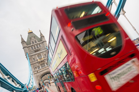 LONDON, UNITED KINGDOM - NOVEMBER 01, 2013: Famous Double-Decker Red Bus on Tower Bridge on a cloudy day