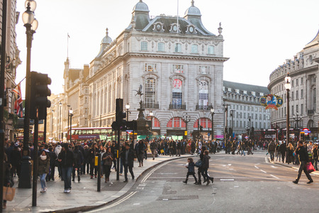 commuters: LONDON, UNITED KINGDOM - OCTOBER 30, 2013: Piccadilly Circus crowded with tourists and commuters at sunset