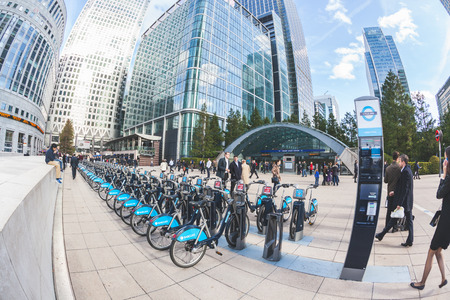 commuters: LONDON, UNITED KINGDOM - OCTOBER 30, 2013: Canary Wharf district with Barclays Cycle Hire docking station and Underground entrance. Many people, tourists and commuters, are walking in the square.