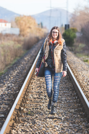 aerea: Beautiful Young Woman Walking on Railway Tracks. The Railroad is in a Residential Aerea. The Girl has a Casual Look.