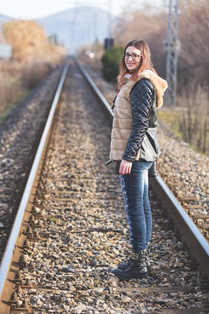 aerea: Beautiful Young Woman Standing on Railway Tracks. The Railroad is in a Residential Aerea. The Girl has a Casual Look. Stock Photo