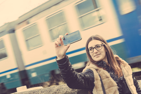passing: Girl Taking Selfie with Train Passing on Background. The Girl is Looking at Smart Phone Camera next to a Rail Crossing; the Train behind is Blurred