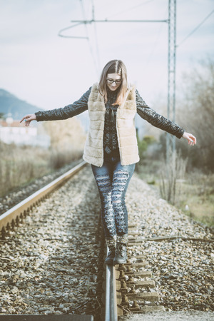 Beautiful Young Woman Walking in Balance on Railway Tracks. The Railroad is in a Residential Aerea. The Girl has a Casual Look.