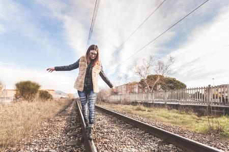 independencia: Bella joven caminando en equilibrio sobre las v�as f�rreas. El ferrocarril se encuentra en una Aerea Residencial. La muchacha tiene un look casual. Foto de archivo