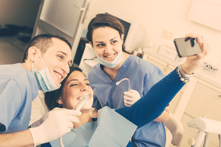 Happy Patient, Dentist and Assistant Taking Selfie All Together. Patient is Holding Smart Phone, Dentist and Assistant are Holding their tools. Focus on Patient Eyes Stock Photo