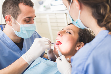 dental office: Dentist and Dental Assistant examining Patient teeth. Dentist is a Man, Assistant and Patient are Women. Patient is Smiling and not scared of Dentist.