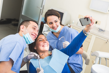 dental clinics: Happy Patient, Dentist and Assistant Taking Selfie All Together. Patient is Holding Smart Phone, Dentist and Assistant are Holding their tools. Focus on Patient Eyes Stock Photo