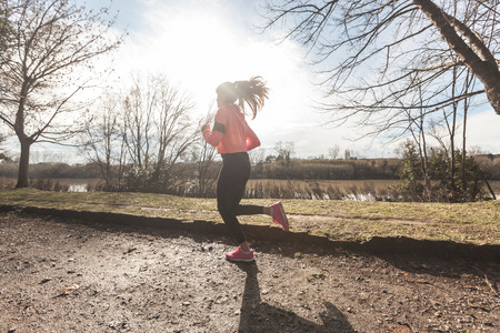 young girl feet: Young Woman Jogging on Off Road Path in the Morning. Natural Setting with a River on background; flares caused by backlight technique. The girl is Wearing Black Leggings and pink Shoes and Sweatshirt