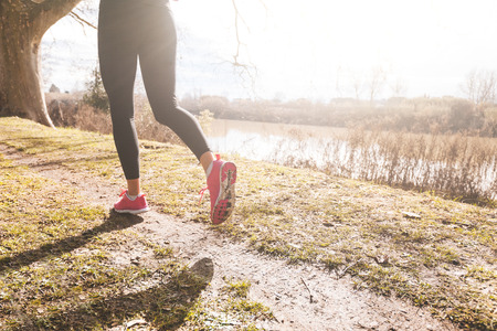 natural setting: Female Runner Legs Closeup on Off Road Path. Natural Setting with a River on background; flares caused by backlight technique. The girl is Wearing Pink Shoes and Black Leggings.