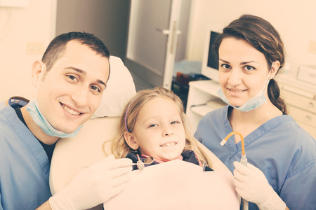 Dentist and Dental Assistant Portrait with Young Patient. Dentist is a Male, Assistant and Patient are Females. All the People are looking at camera with Smiling Expressions. photo