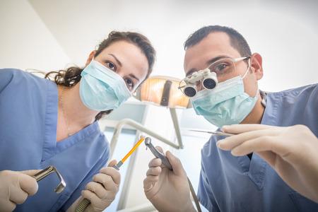taladro: Alegres Dentistas Herramientas Holding dentales mirando a cámara. Punto Personal o Paciente de vista, POV. Ellos son la celebración de taladro, Espejo, aspirador y esparcidor. Dentista lleva dentales lupas.