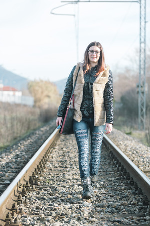 Beautiful Young Woman Walking on Railway Tracks. The Railroad is in a Residential Aerea. The Girl has a Casual Look.