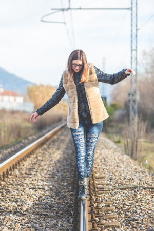 aerea: Beautiful Young Woman Walking in Balance on Railway Tracks. The Railroad is in a Residential Aerea. The Girl has a Casual Look.