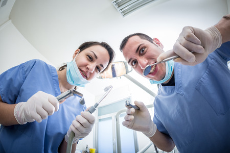 fear: Dentists Holding Dental Tools Looking at Camera with Scary Faces. Personal or Patient Point of View, POV. Dental Fear theme. Stock Photo