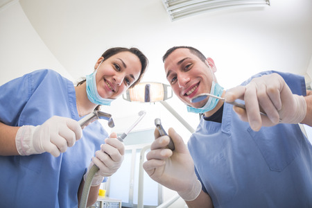 aspirator: Cheerful Dentists Holding Dental Tools Looking at Camera. Personal or Patient Point of View, POV. They are holding Drill, Mirror, Aspirator and Spreader.