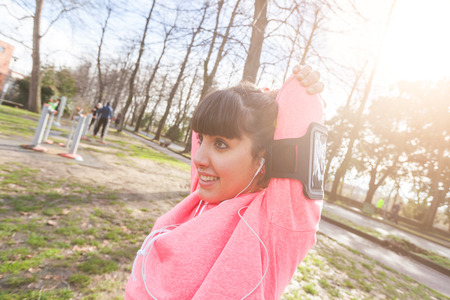 Young Woman Doing Arms and Shoulders Stretching Exercises. She Has a Smart Phone Holder on the Left Arm and she is Listening Music with Earphones. Urban Park setting. Stock Photo - 36473910