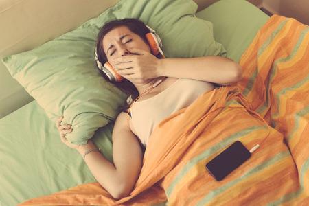 perezoso: Mujer joven que escucha la m�sica con los auriculares en la cama. Foto de archivo