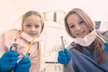 farce: Little Female Dentists Holding Dental Tools Looking at Camera. Personal or Patient Point of View, POV.  Stock Photo