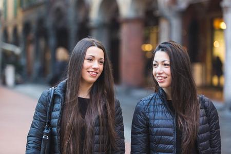 inner city: Female Twins Walking on Inner City Street.  Stock Photo