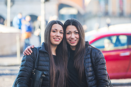 twin house: Female Twins Portrait in the City with Traffic on Background.