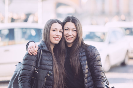 Female Twins Portrait in the City with Traffic on Background.  photo