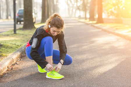crouched: Young Sporty Woman Doing Up her Shoes Before Running. She wears Glow Yellow Shoes. The Girl is Crouched on Footpath, Backlight Setting. Stock Photo