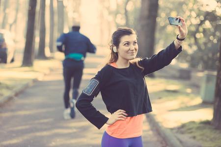 gimnasio mujeres: Joven Mujer Deportiva Tomando un Autofoto en el Parque. Foto de archivo