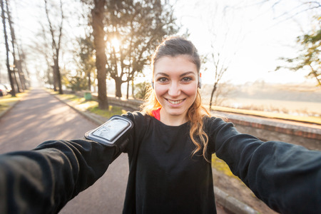 woman sport: Young Sporty Woman Taking a Selfie at Park. She is Looking at Camera, that is the POV