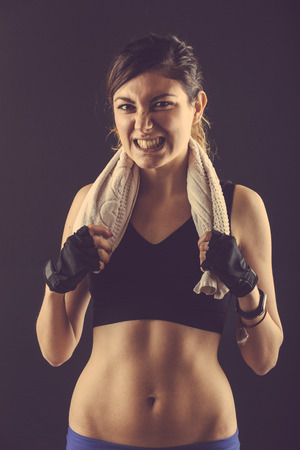 grinding teeth: Sporty Young Woman Grinding Teeth on Black Background. Shes is Wearing a Black Top and she is Holding with the Hands a Towel around her Neck.
