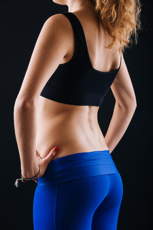 bum: Sporty Female Bum and Back on Black Background. She is standing with Hands on Hips, Wearing Leggings and Top. Close Up shot. Stock Photo