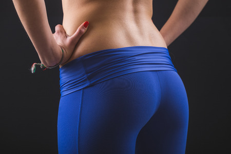 black ass: Sporty Female Bum and Back on Black Background. She is standing with Hands on Hips, Wearing Leggings and Top. Close Up shot. Stock Photo