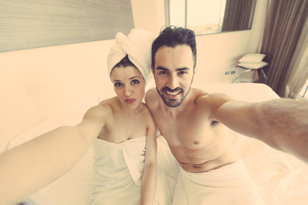 shower head: Couple Taking Selfie after Shower. They are in a Modern Hotel Room, They wear white towels and the Woman also has a towel around her Head. They hold the Smart Phone together and Look at it.