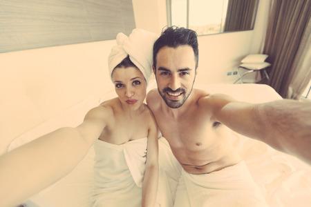 mujer bañandose: Pares que toman Autofoto después de la ducha. Ellos están en un moderno hotel de habitaciones, llevan toallas blancas y la mujer también tiene una toalla alrededor de su cabeza. Llevan a cabo el Móvil juntos y mire.